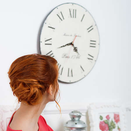 career timing: young, beautiful girl in a red dress watch on clock