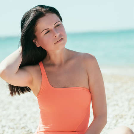 Woman rest on a beach. Portrait of the beautiful girl close-up, the wind fluttering hair.