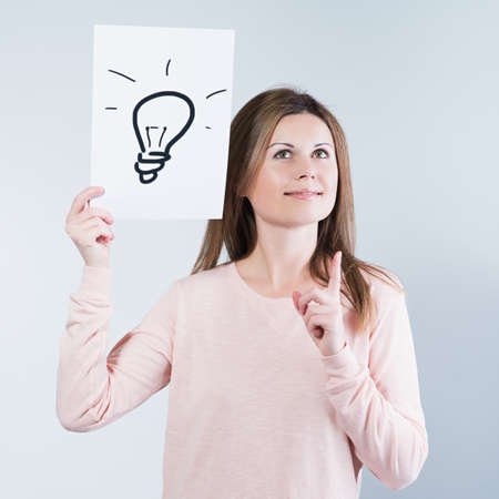 Young woman holding a paper with light bulbs.