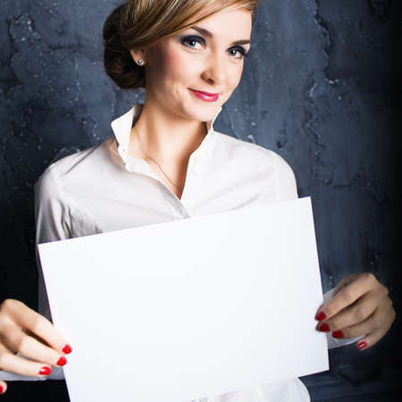 Businesswoman holding a white poster and smiling.