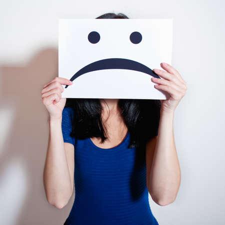 cara triste: Mujer que sostiene un papel en blanco con cara triste Foto de archivo