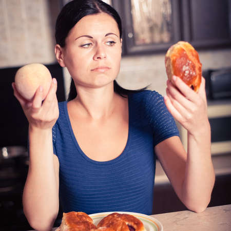 care about the health: Young woman chooses between a peach and pie. Care about health