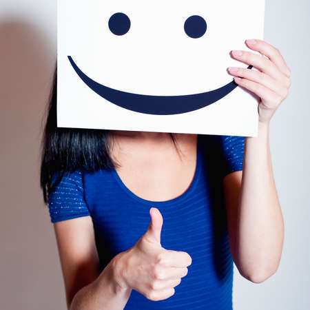 Young woman holds a smile, thumbs up