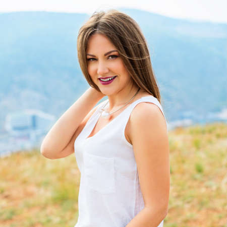 warm shirt: Beautiful modern woman with long hair in a white shirt and blue jeans  outdoors. Smiling girl enjoys fine warm spring weather highly in mountains against the sea.  Stock Photo