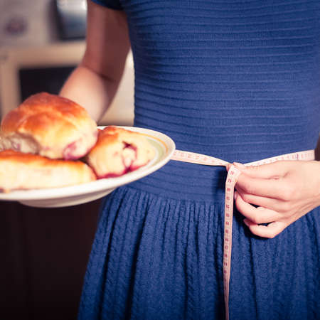 munching: young woman holds pie and a measuring tape, care about health Stock Photo