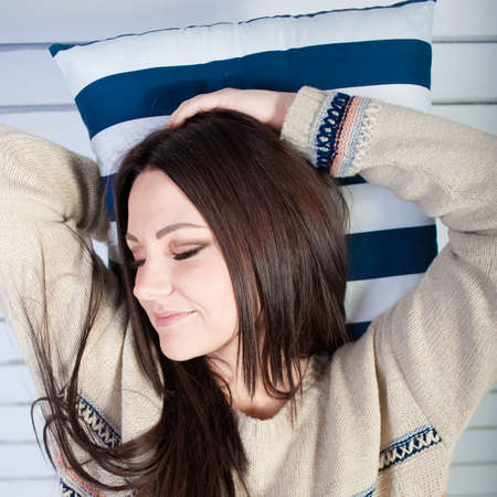 sleeps: The young girl in a warm sweater with pleasure sleeps on a soft pillow