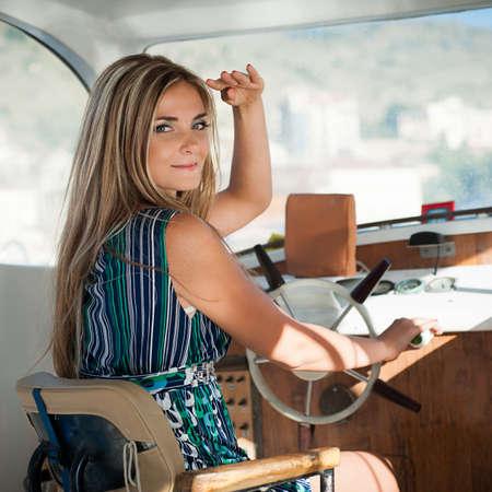 operates: giovane, bella donna gestisce lo yacht, si presenta in una distanza Archivio Fotografico