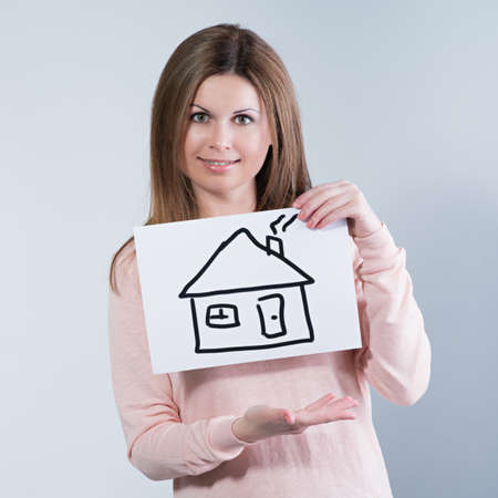 young woman holding picture with house Stock Photo