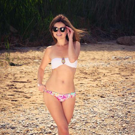 Young woman on a beach in bikini and sunglasses. model posing
