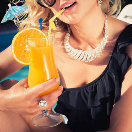 beautiful, suntanned, young woman drinks cocktail, and enjoys in the summer afternoon near the pool.