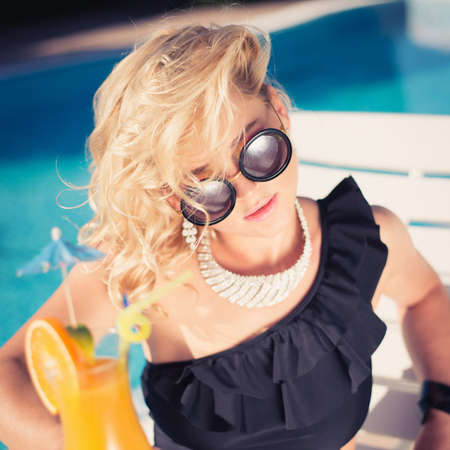 suntanned: beautiful, suntanned, young sexy woman drinking cocktail, and enjoys in the summer afternoon near the pool. Stock Photo