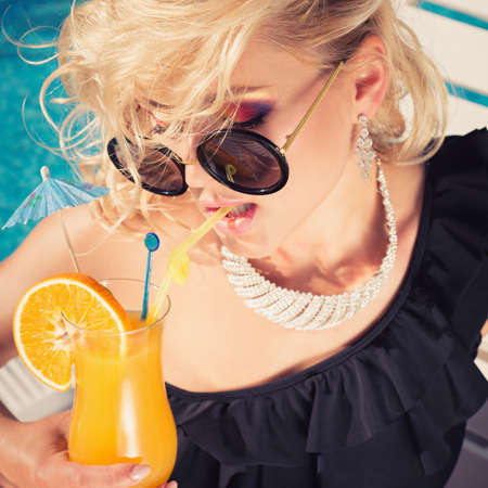 suntanned: beautiful, suntanned, young sexy fashion woman drinking cocktail, and enjoys in the summer afternoon near the pool.