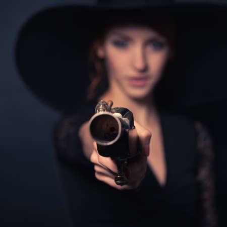 musket: girl pirate with ancient pistol in hand on a black background Stock Photo