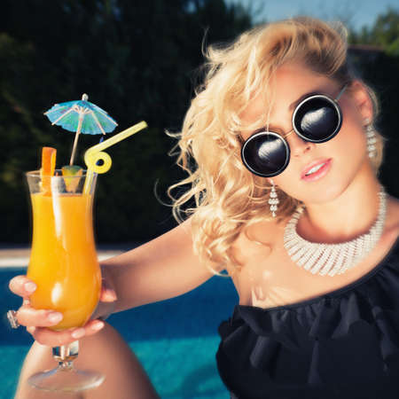 suntanned: beautiful, suntanned, young woman drinking cocktail, and enjoys in the summer afternoon near the pool. Photo toned style instagram filters Stock Photo