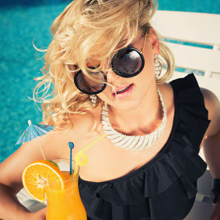 suntanned: beautiful, suntanned, young sexy woman drinking cocktail, and enjoys in the summer afternoon near the pool.