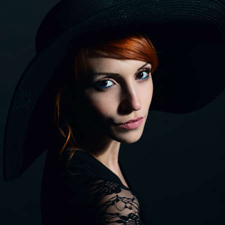 Portrait of a very beautiful girl in black dress and hat. Vogue style.