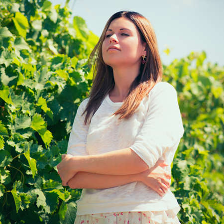 beautiful young woman, walks on a vineyard in a hot summer, sunny day. Photo with instagram style filters