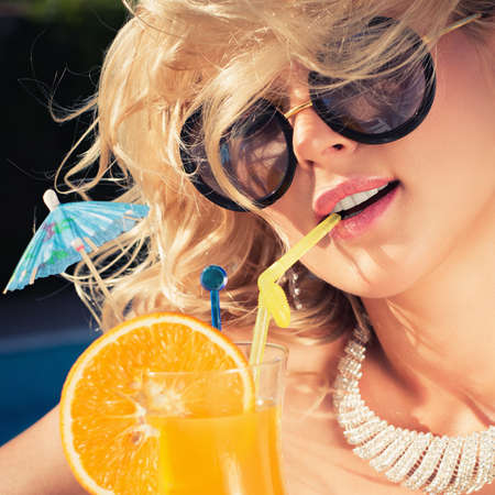 beautiful, suntanned, young woman drinks cocktail, and enjoys in the summer afternoon near the pool