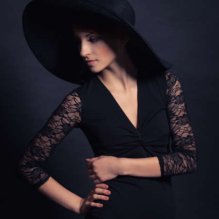 Portrait of a very beautiful girl in black dress and hat. Vogue style