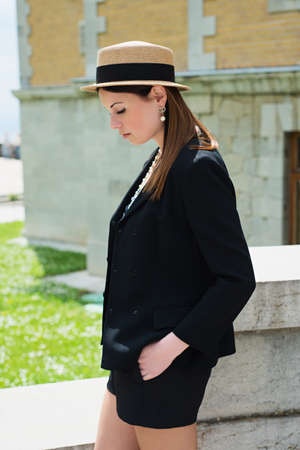 Stylish Parisian woman poses on a photoshoot. Fashion style portrait of young trendy girl walking along the street