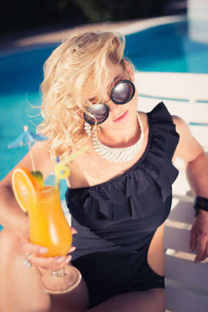 beautiful, suntanned, young sexy woman drinking cocktail, and enjoys in the summer afternoon near the pool. young sexy fashion woman drinking cocktail