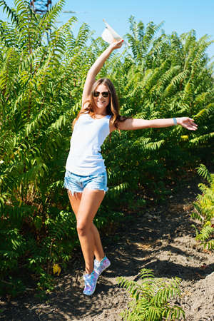 Cheerful fashionable woman in stylish hat and jeans shorts posing. Hipster style. girl with long hair poses in warm spring day