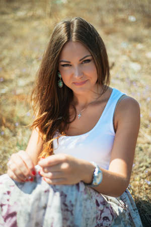 Portrait of the young beautiful smiling woman outdoors enjoying summer sun. wind in hair Stock Photo