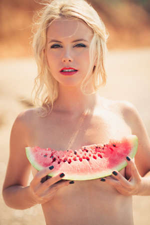 young beautiful girl, attractive blonde, enjoys tropical weather, eats a water-melon, wind develops beautiful long hair