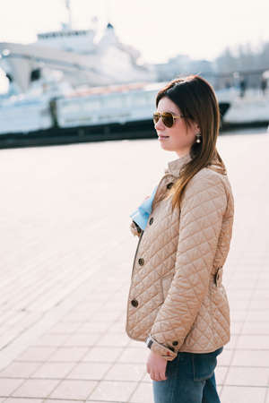Outdoor lifestyle portrait of woman walking at coast. Fashion style. young woman dressed in branded clothes enjoys warm, spring weather Stock Photo