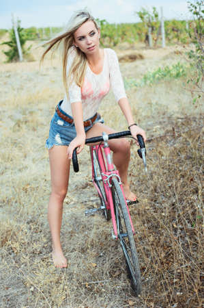 Young pretty blonde woman posing  in summer sunshine. hipster. bike