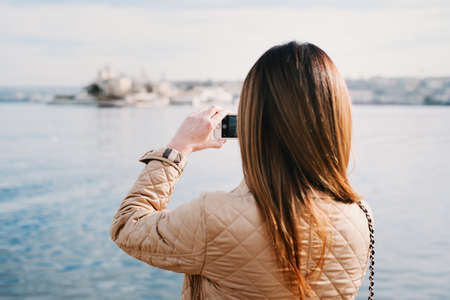Fashion  woman taking photo with cellphone on the coast on spring. Happy girl on vacation taking picture on sea background.