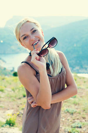 portrait of the attractive, slender, beautiful young Caucasian  blonde girl. Smiling girl enjoys fine warm summer weather highly in mountains against the sea