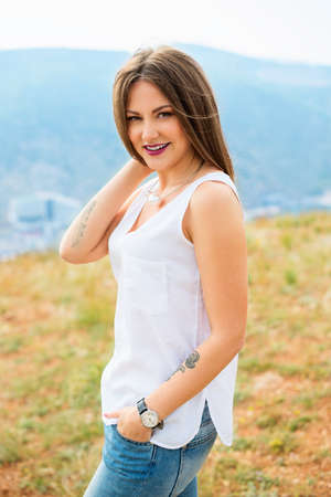 Beautiful modern woman with long hair in a white shirt and blue jeans  outdoors. Smiling girl enjoys fine warm spring weather highly in mountains against the sea