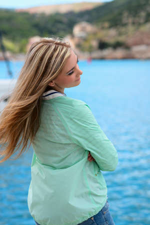 young adult lady enjoying summer travel. European girl tourist traveling in sail boat around the world
