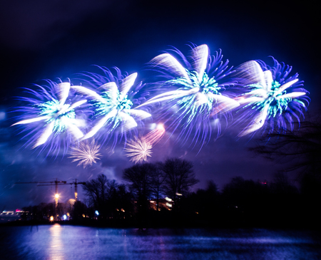 Abstract, blurry, bokeh-style colorful photo of fireworks above the river in New Year