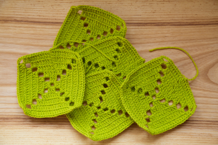 A beautiful hand crocheted pattern pieces of vibrant color gradient in  green tones