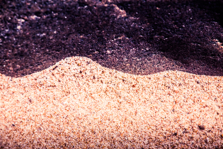An abstract, high contrast background of a sea sand and rock shapes. Shallow depth of field, purple color tone.
