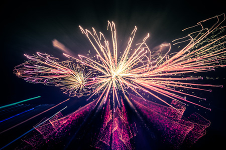 pyrotechnics: Abstract, blurry, bokeh-style colorful photo of fireworks in a purple tone above the river