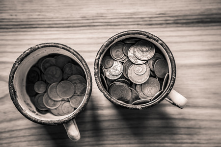 Old soviet coins in a rusty enamel cup on a wooden background