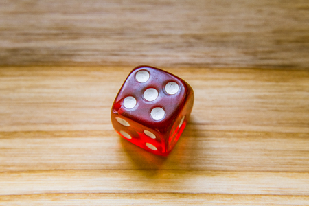 A beautiful winning playing dice rolled on a side on wooden table