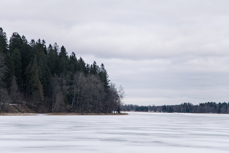 frozen lake: A peaceful winter landscape with a frozen lake in overcast day