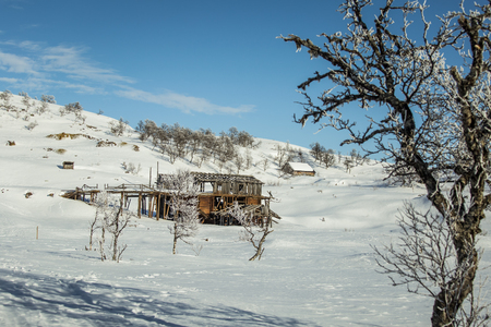 An old, abandoned copper mine building in the snowy Norway landscape