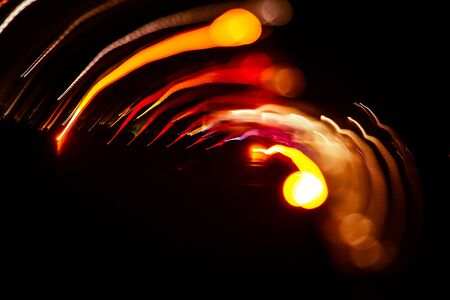 Red abstract trails of light on dark background. Long exposure. Stock Photo