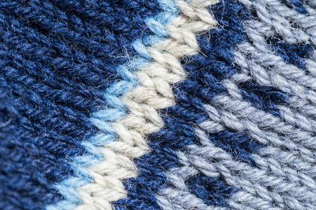 navy blue background: A beautiful closeup of a hand knitted warm and soft wool pattern. Soft socks or scarf of natural wool. Colorful pattern.