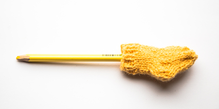 Small, hand knitted woolen socks with a color pencils on light background