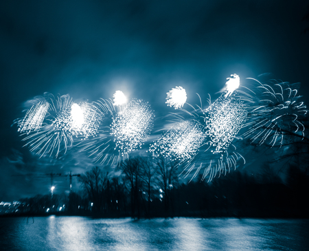 Abstract, blurry, bokeh-style colorful photo of fireworks in a blue tone above the river Stock Photo