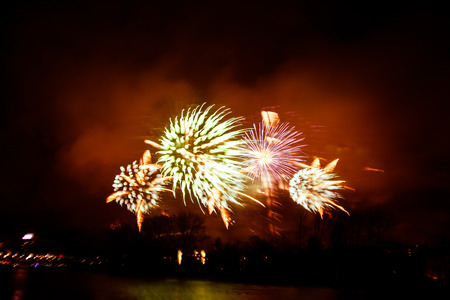 pyrotechnics: Abstract, blurry, bokeh-style colorful photo of fireworks in a red tone above the river