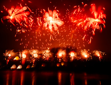 Abstract, blurry, bokeh-style colorful photo of fireworks in a red tone above the river