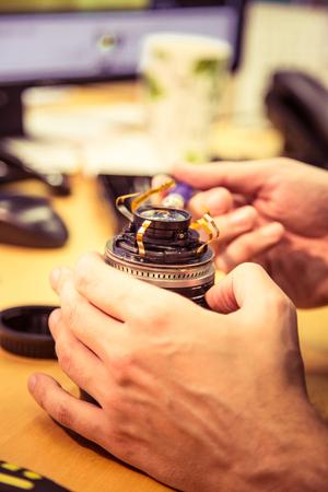 Een mens die de lens van de fotocamera op een bureaulijst bevestigt