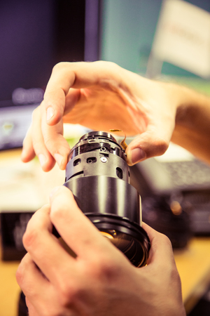 A man fixing photo camera lens on an office table